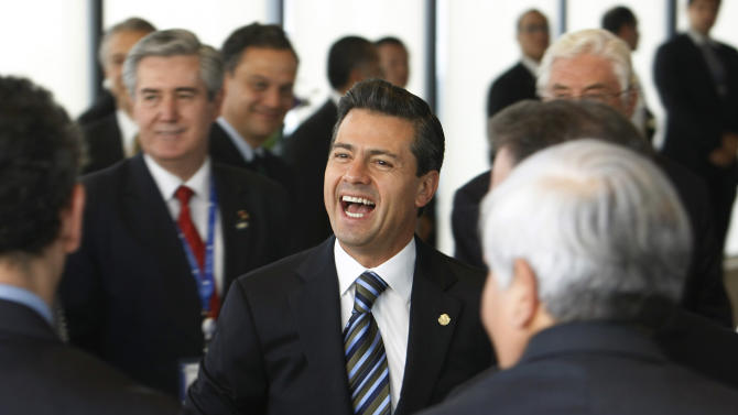 Mexico's President Enrique Pena Nieto laughs as he meets with members of the Economic Commission for Latin America and the Caribbean in Santiago, Chile, Friday, Jan. 25, 2012. Leaders from the European Union, Latin America and the Caribbean are gathering in Santiago for the CELAC-EU economic summit Jan 26-27. (AP Photo/Victor Ruiz Caballero)