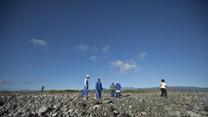 Workers for an association responsible for maintaining paths to the beaches from being overgrown by shrubs, search the beach for possible additional airplane debris near the area where an airplane wing part was washed up, in the early morning near to Saint-Andre on the north coast of the Indian Ocean island of Reunion Friday, July 31, 2015. A barnacle-encrusted wing part that washed up on the remote Indian Ocean island could help solve one of aviation's greatest mysteries, as investigators work to connect it to the Malaysia Airlines Flight 370 that vanished more than a year ago with 293 people aboard. (AP Photo/Ben Curtis)