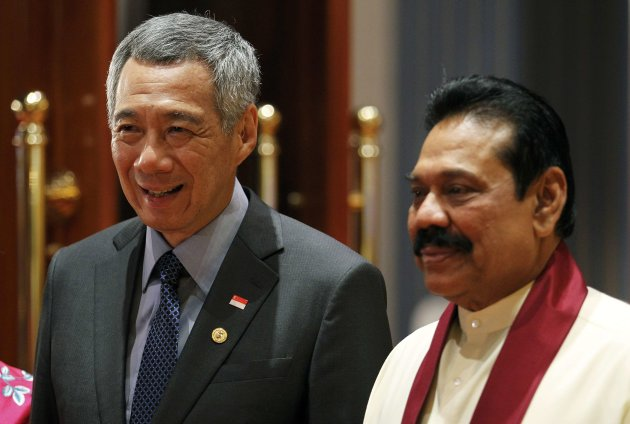 Singapore's Prime Minister Lee Hsien Loong (L) poses for a photo with Sri Lanka's President Mahinda Rajapaksa during a banquet dinner for the Commonwealth Heads of Government Meeting (CHOGM) in Colombo November 16, 2013. REUTERS/Dinuka Liyanawatte (SRI LANKA - Tags: POLITICS)