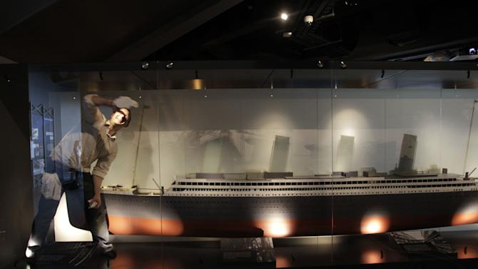 A man cleans glass around a large replica of the Titanic on display in Titanic House Vistor Centre, Belfast, Northern Ireland, Tuesday, March, 27, 2012.  The £100 million (119.5 million euros; $158 million dollars) building is now finished and will open to the public on March 31. The world's biggest Titanic visitor attraction is to open in its Belfast birthplace later this month and it is  100 years to the day since the doomed ocean liner was completed in the same shipyard, Harland and Wolff.  Northern Ireland hopes the eye-catching building will boost the tourism economy.  (AP Photo/Peter Morrison)