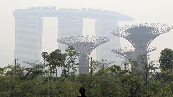"""This photo taken on Monday, June 17, 2013 shows the Marina Bay Sands hotel and the Supertrees at Gardens By The Bay covered in haze.  The Pollutant Standards Index, Singapore's main measure to determine air quality, crept into the """"unhealthy"""" classification Monday as smoke from roaring blazes on Indonesia's Sumatra island drifted across the sea and cast a gray pall over the city-state's skyscrapers. (AP Photo/Wong Maye-E)"""