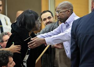 Jonathan Fleming, left, reaches to hug his mother Tricia …