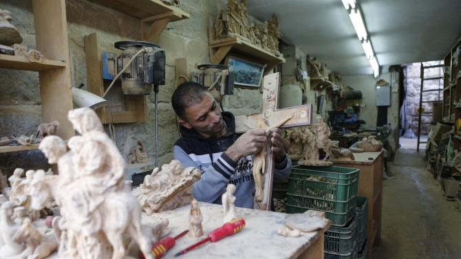 A Palestinian sculptor carves models of the Holy Family from olive wood in a workshop, ahead of Christmas in the West Bank city of Bethlehem