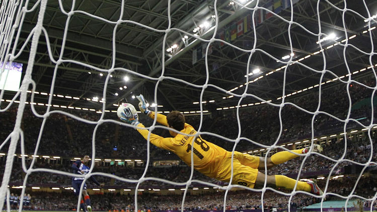 South Korea's Lee Bum-young saves on a decisive penalty by Britain's Daniel Sturridge, left, during a men's soccer quarterfinal match between, at the Millennium stadium in Cardiff, Wales, at the 2012 London Summer Olympics, Saturday, Aug. 4, 2012. South Korea won 5-4 after penalties and advances to the semifinals. (AP Photo/Luca Bruno)