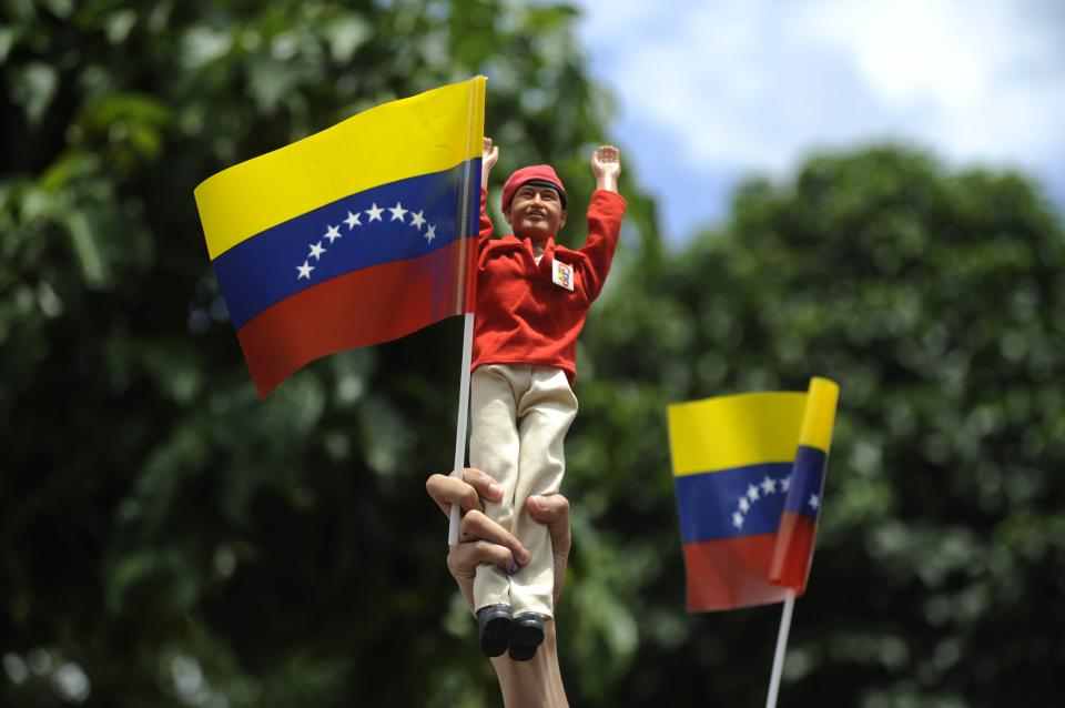 A supporter holds up a doll of Venezuela's President Hugo Chavez while waiting for his arrival to a polling station during the presidential election in Caracas, Venezuela, Sunday, Oct. 7, 2012. Chavez is running for re-election against opposition candidate Henrique Capriles. (AP Photo/Sharon Steinmann)