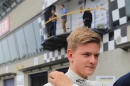 German Formula 4 driver Mick Schumacher of team Van Amersfoort walks with his best rookie award during the season kickoff in Oschersleben, Germany, Saturday, April 25, 2015, after ranking 9th in the race. He is the son of former Formula One World Champion Michael Schumacher. (Jens Wolf/dpa via AP)