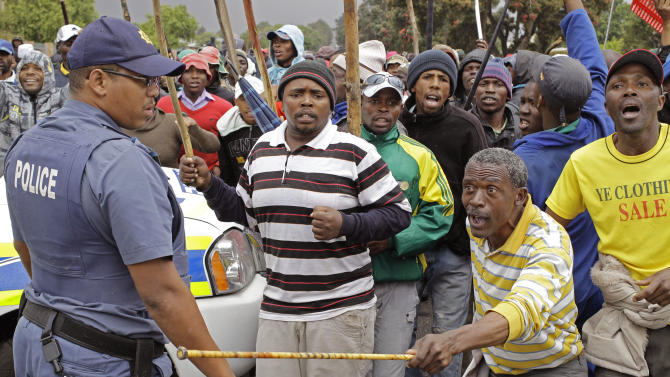 A South African Policeman, left,  provide security as farm workers demonstrate due to low wages in the town of Grabouw, South Africa, Wednesday, Jan 9, 2013. Striking farm workers on Wednesday set up barricades and threw stones at motorists and police in a South African province whose vineyards are vital to the wine industry, prompting riot officers to close roads and arrest at least 50 demonstrators, South African media reported. (AP Photo/Schalk van Zuydam)