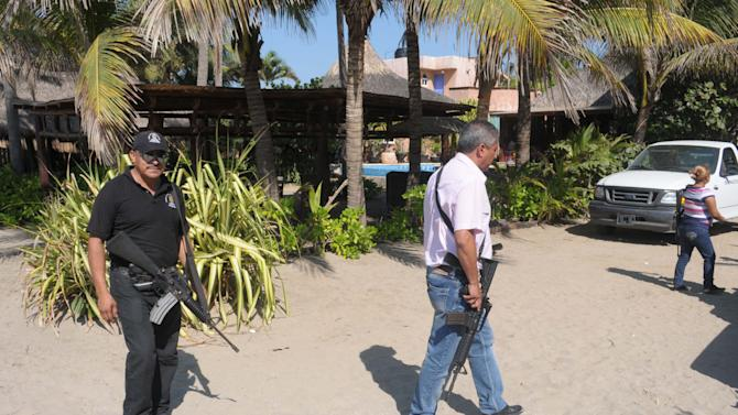 Police patrol on the beach outside a home after masked armed men broke into the home in Acapulco, Mexico, Tuesday Feb. 5, 2013. According to the mayor of Acapulco, five masked men burst into the house that Spanish tourists had rented on the outskirts of Acapulco, in a low-key area near the beach, and held a group of six Spanish men and one Mexican woman at gunpoint, while they raped the six Spanish women before dawn on Monday. (AP Photo/Bernandino Hernandez)