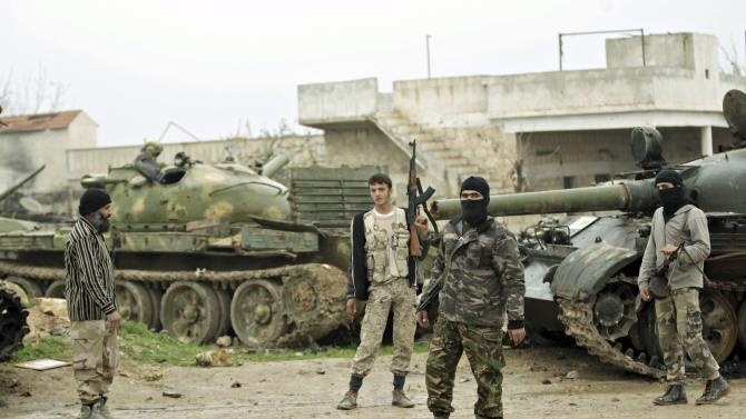 Ahrar al-Sham Islamic fighters stand beside tanks left behind by forces loyal to Syria's president Bashar Al-assad in al-Hamidiyeh base, in the southern Idlib countryside