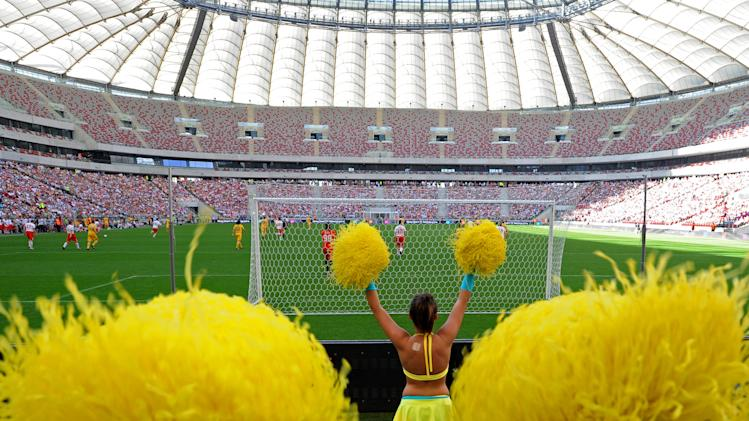 Cheerleaders dressed in Ukrainian national colors dance as Polish and Ukrainian celebrities play a friendly soccer match at the National Stadium in Warsaw, Poland, Sunday, April 29, 2012. The game was the last event at the site before the opening of the Euro 2012 soccer championships, which will open in this stadium. (AP Photo/Alik Keplicz)