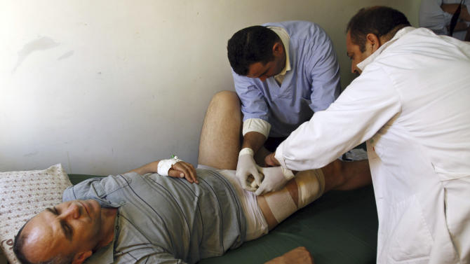 Palestinian lawmaker Shami Al-Shami, 47, is treated by medics for gun wounds sustained outside his home in the West Bank town of Jenin, Sunday, July 1, 2012. Al-Shami said Sunday he has been shot twice in the leg by assailants as he got out of his car outside his home. Jenin once served as a model for Palestinian law and order, but has experienced a wave of brazen attacks by gunmen over the past year. (AP Photo/Mohammed Ballas)