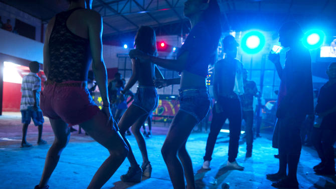 """In this Dec. 8, 2012 photo, people dance during a funk """"baile,"""" or party, in a slum in western Rio de Janeiro, Brazil. A 2007 law that had made it virtually impossible to hold the traditional open-air funk parties in favelas was repealed in 2009, and the musical genre was recognized as a """"cultural movement."""" Dance face-offs between performers of """"passinho,"""" a type of break dancing associated with Rio's funk scene, now come with corporate sponsorship. (AP Photo/Felipe Dana)"""
