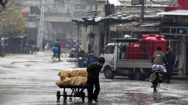 A child walks as he drags wood under the rain in eastern Ghouta
