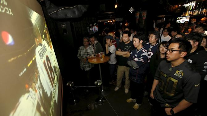 Fans watch a screen showing Denver Broncos' quarterback Manning during the NFL's Super Bowl 50 between Carolina Panthers and Denver Broncos during its live telecast in Tokyo