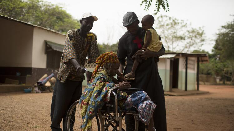 Father Kenvi talks to a disabled Muslim woman as he holds a child that was found alone in the forest, at the John Paul II Catholic mission in the town of Bossemptele