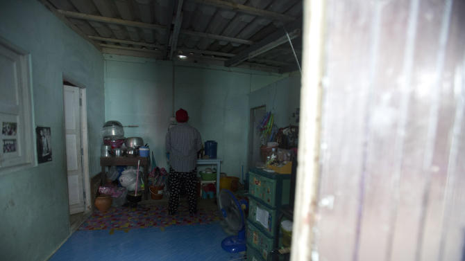 In this Friday, Aug. 29, 2014 photo, Wassana stands in a rented room in Bangkok,Thailand. When the young Thai woman saw an online ad seeking surrogate mothers, it seemed like a life-altering deal: $10,000 to help a foreign couple who wants a child but can't conceive. Wassana, a lifetime resident of the slums, viewed it as a nine-month solution to her family's debt. She didn't ask many questions. (AP Photo/Sakchai Lalit)