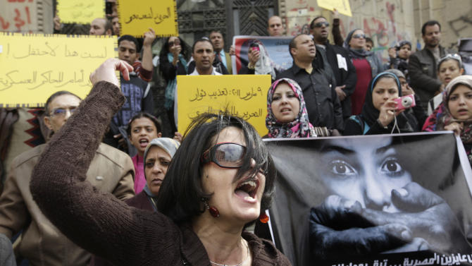 """An Egyptian activist shouts anti-military Supreme Council slogans during a demonstration in front of Cairo's high court, Egypt,  Friday, March 16, 2012 as they protest against a military tribunal verdict acquitting an army doctor of an accusation of public obscenity filed by a protester who claimed she was forced to undergo a virginity test while in detention among seven women detained by the military a year ago. Arabic reads """" March 9, 2011, protesters torture """" and  """" We did not want the Egyptian woman to be a second-class citizen"""".   (AP Photo/Amr Nabil)"""