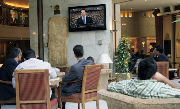 "People watch Syrian president Bashar Assad deliver a live speech in Damascus, Syria, Sunday, June 3, 2012. Assad says his government had nothing to do with the Houla massacre, saying not even ""monsters"" would carry out such an ugly crime. The speech Sunday marked Assad's first comments on the killings. (AP Photo/Bassem Tellawi)"