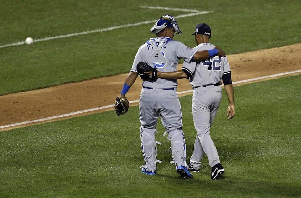 American League's Mariano Rivera, of the New York Yankees, walks off the field with catcher American League's Salvador Perez, of the Kansas City Royals, after pitching during the eighth inning of the MLB All-Star baseball game, on Tuesday, July 16, 2013, in New York. (AP Photo/Julio Cortez)