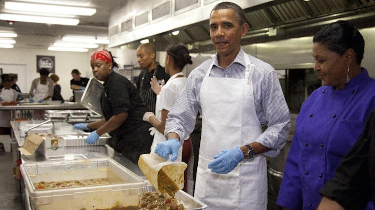 President Barack Obama participates in a service project Saturday, Sept. 10, 2011, at the DC Central Kitchen in Washington to commemorate the September 11th National Day of Service and Remembrance. At right is DC Central employee Marianne Ali. The First Family helped prepare a meal of chicken sausage gumbo, rice, a garden salad and cantaloupe wedges. (AP Photo/Carolyn Kaster)