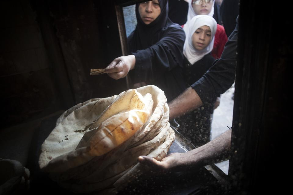 In this Saturday, Sept. 22, 2012 photo Syrians buy bread in a bakery in the Saif al Dawla neighborhood of Aleppo, Syria. (AP Photo/ Manu Brabo)