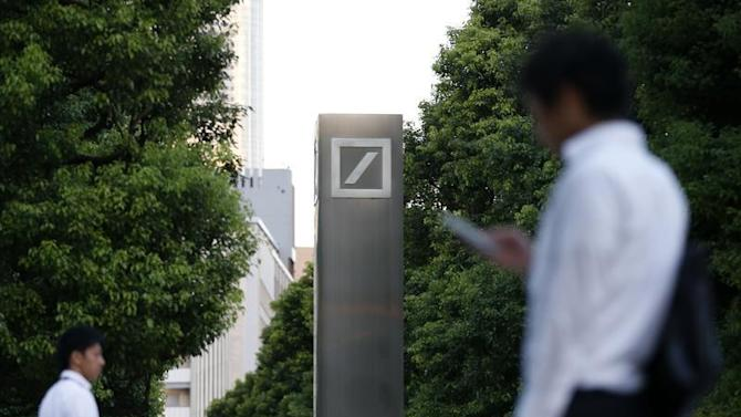 Men walk past logo of Deutsche Bank AG in Tokyo