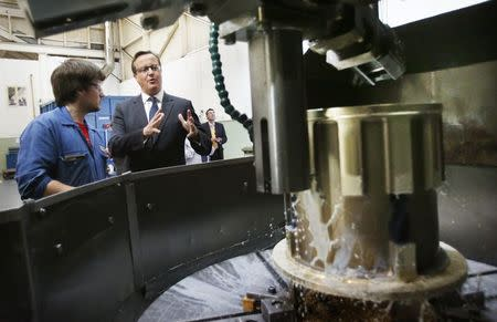 Britain's Prime Minister David Cameron speaks to a worker during a visit to engineering company MacTaggart Scott in Edinburgh
