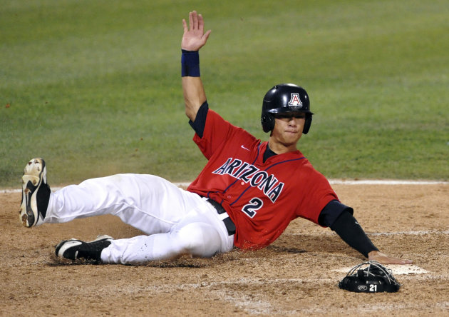 Arizona&#39;s Robert Refsnyder scores against South Carolina on a single by Bobby Brown in the seventh inning of Game 1 of the NCAA College World Series baseball finals in Omaha, Neb., Sunday, June 24, 2012. (AP Photo/Dave Weaver)