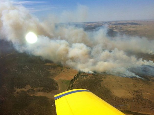 In this photo provided by the New South Wales Rural Fire Service, plumes of smoke rise from a fire near Cooma, Australia, Tuesday, Jan. 8, 2013. Temperatures across much of New South Wales state are e