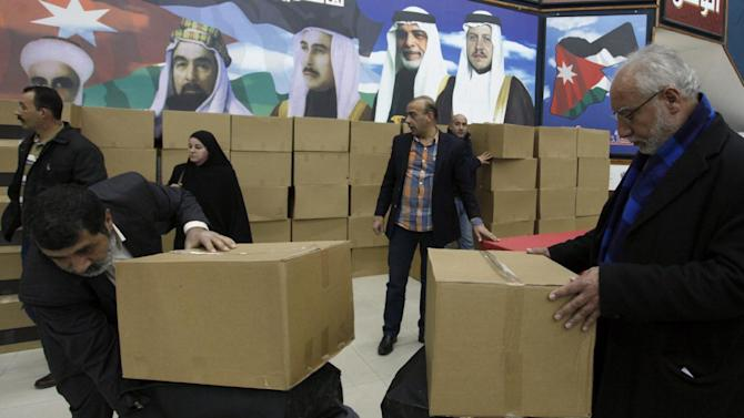Members of the Jordanian Independent Electoral Commission check boxes of ballots to be distributed to the polling stations, one day before the designated date of the Jordanian parliamentary elections, in Amman, Jordan, Tuesday, Jan. 22, 2013. King Abdullah II is trying to control the pace of change, ceding enough of his absolute powers to parliament in hopes of forestalling any Arab Spring-style uprisings like the ones that toppled autocratic leaders in Egypt, Libya, Yemen and Tunisia and devolved into a bloody civil war in Syria. But the Muslim Brotherhood and others in the opposition say his moves do not go far or fast enough to end his monopoly on power. The portraits in the background are of the Kings of Jordan, with the current King Abdullah II, right. (AP Photo/Mohammad Hannon)