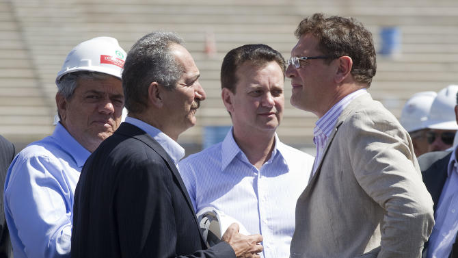 Brazil's Sports Minister Aldo Rebelo, second left, Sao Paulo's Mayor Gilberto Kassab, center,  and FIFA Secretary General Jerome Valcke, right, make a visit to the Corinthians stadium, which is under construction and will host the opening match of the World Cup in 2014 in Sao Paulo, Brazil, Wednesday, Nov. 28, 2012. Officials are revising the construction work being done at stadiums ahead of the Confederations Cup soccer tournament in 2013 and the 2014 FIFA World Cup soccer tournament. (AP Photo/Andre Penner)