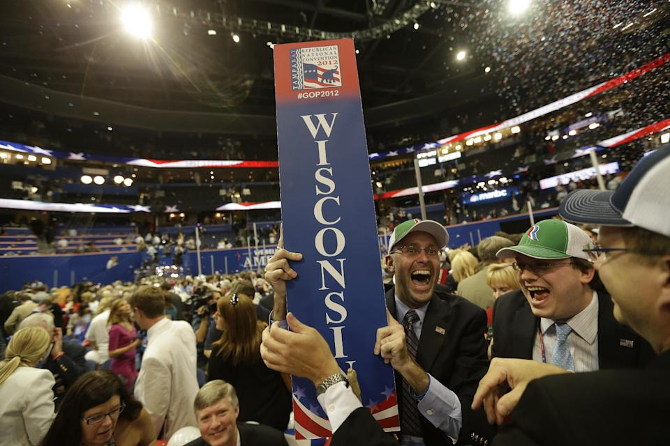 Justin Johnson of Chippewa Falls, Wis., celebrates after removing his state's sign after Republican presidential candidate Mitt Romney and vice presidential candidate Paul Ryan left the stage at the end of the Republican National Convention in Tampa, Fla., on Thursday, Aug. 30, 2012. (AP Photo/David Goldman)