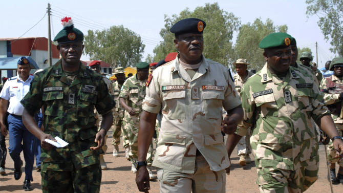 Maj. Gen. Kenneth Osuji, commander of the Nigeria Army peace keeping center, left, Maj. Gen. John Zaruwa, commander of the Nigeria peace keeping center, and Lt. Gen. Onyeabo Azubike Ihejirika, Nigeria chief of army staff, right, inspect Nigeria battalion 1 troops before their departure, at the peace keeping center in Jaji, Kaduna, Nigeria, Thursday, Jan. 17, 2013. The Federal Government has approved the immediate deployment of 900 troops as part of the ECOWAS  (Economic Community of West African States ) force to push for the emancipation of Northern Mali from the grip of Islamists. (AP Photo)