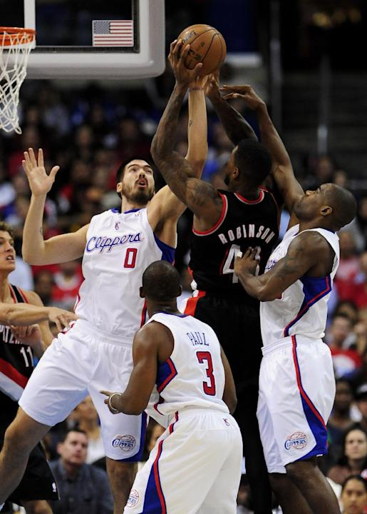 Double teamed by Los Angeles Clippers center Byron Mullens (0), forward Antawn Jamison, right, Portland Trail Blazers forward Thomas Robinson (41) attempts the shot as Los Angeles Clippers guard Chris