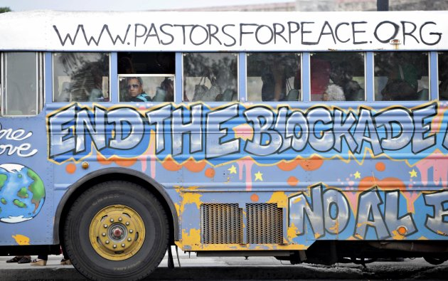 A man sits in a bus donated by the Pastors of Peace adorned with graffiti demanding an end to the U.S. trade embargo on Cuba in Havana