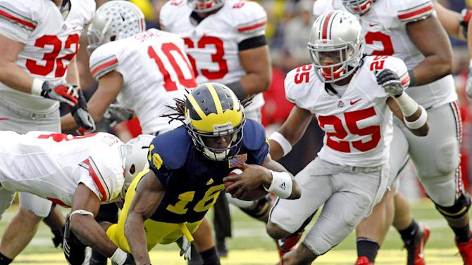 Michigan quarterback Denard Robinson (16) is tripped up by Ohio State defensive back C.J. Barnett, left, alongside defensive back Bradley Roby (25) in the fourth quarter of an NCAA college football game, Saturday, Nov. 26, 2011, in Ann Arbor. Michigan won 40-34. (AP Photo/Tony Ding)