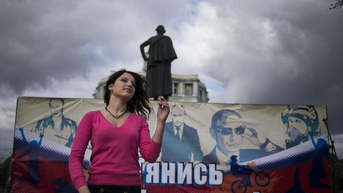 """An activist of the Pro-Kremlin youth movement, Mestnye (locals), dances in front of a poster reading """"Tighten with Putin"""" celebrating the 60th birthday of Russian President Vladimir Putin in Moscow, Sunday, Oct. 7, 2012, with the statue of Alexander Suvorov in the background. Vladimir Putin turns 60-years old on Sunday, Oct. 7, 2012, and has recently sought to demonstrate his youthful vigor by many personal endeavors, but while he has shown creativity in his action-man stunts, the Russian president seems surprisingly vulnerable to the vagaries of oil prices.(AP Photo/Alexander Zemlianichenko)"""
