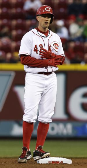 Cincinnati Reds starting pitcher Mike Leake adjusts his gloves while standing on second base after hitting a double off Pittsburgh Pirates starting pitcher Gerrit Cole in the third inning of a baseball game, Tuesday, April 15, 2014, in Cincinnati. (AP Photo/Al Behrman)