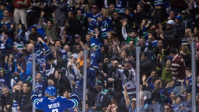 Vancouver Canucks' Yannick Weber, of Switzerland, celebrates his goal against the St. Louis Blues during the first period of an NHL hockey game in Vancouver, British Columbia,  on Sunday March 1, 2015.  (AP Photo/The Canadian Press, Darryl Dyck)