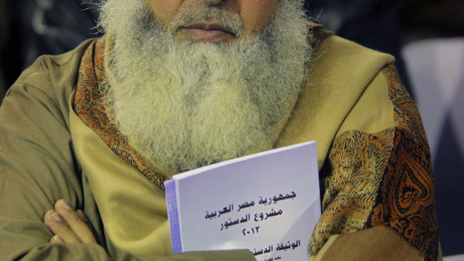 """In this Thursday, Jan. 9, 2014 photo, an Egyptian Salafi holds a copy of the new constitution as he attends a conference to hear a lecture entitled """"Know Your Constitution,"""" ahead of a two-day vote on a draft amendment in El-Saf village, 50 kilometers (31 miles) south of Cairo, Egypt. Arabic reads, """"the constitution of the Arab Republic of Egypt."""" The conference, held to rally """"yes"""" votes for the charter, highlights a striking alliance that has emerged since the military toppled Islamist President Mohammed Morsi and his democratically elected government last summer. Both the military-backed authorities and the Al-Nour party appear to be benefiting from it, despite the awkwardness. (AP Photo/Amr Nabil)"""