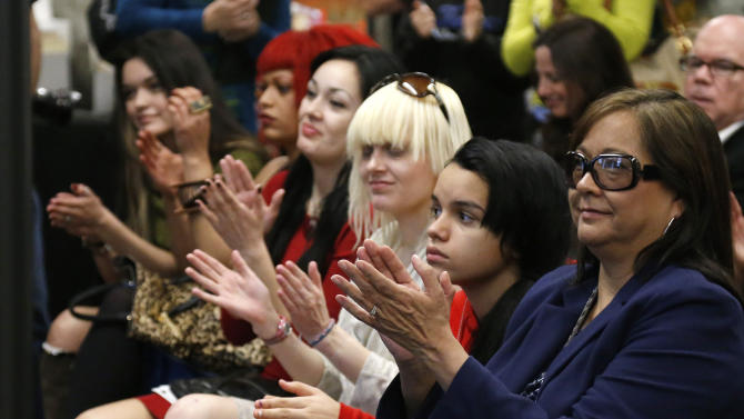 Jan Bridges, wife of musician Leon Russell, right, applauds with other family members during a news conference in Tulsa, Okla., Tuesday, Jan. 29, 2013. The Oklahoma Historical Society has acquired a large collection of works by the legendary musician and native Oklahoman that are intended for display in a planned pop culture museum in Tulsa. (AP Photo/Sue Ogrocki)