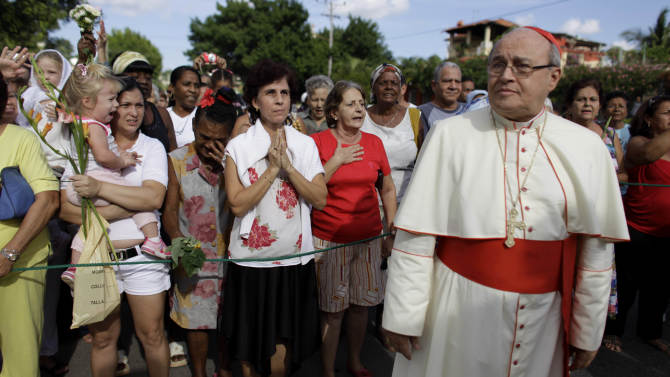 FILE - In this Nov. 10, 2011 file photo, Cuba's Cardinal Jaime Ortega attends a procession honoring the nation's patron saint, the Virgin of Charity of Cobre, in Havana, Cuba. For months, Ortega has been under fire: called a lackey and political ally of Raul Castro's communist government, asked to resign over his treatment of protesters and ridiculed in Miami as a snobby elitist. Church officials on the island have launched a full-throated defense of their leader, and Catholic publications have harshly denounced his critics. Analysts say the increasingly virulent back-and-forth is extremely unusual on an island where the church has traditionally preferred to exercise influence quietly, behind the scenes. (AP Photo/Javier Galeano, File)