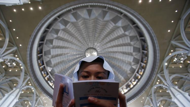 A woman reads a booklet containing verses from the Koran during a special prayer for victims of Malaysia Airlines Flight MH17, inside the Tuanku Mizan Zainal Abidin mosque in Putrajaya