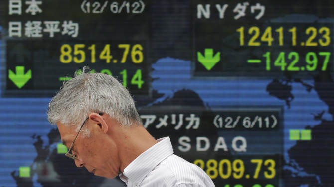 A man uses his mobile phone in front of the electronic stock board of a securities firm in Tokyo, Tuesday, June 12, 2012. Asian stock markets slid Tuesday as enthusiasm for a European plan to rescue Spain's teetering banks turned to skepticism. Japan's Nikkei 225 index fell 1.3 percent to 8,514.76. (AP Photo/Itsuo Inouye)