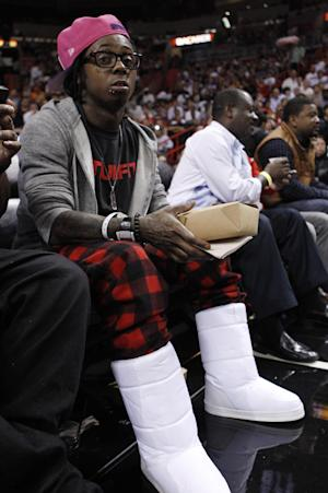 "FILE - In this Jan. 27, 2012 file photo, Rapper Lil Wayne sits courtside during an NBA basketball game between the Miami Heat and New York Knicks, in Miami. The Thunder say Lil Wayne is welcome to attend a playoff game in Oklahoma City, but needs to buy a ticket just like everyone else. The rapper created a stir Thursday, May 31, 2012 by posting on Twitter that he was ""going to go to the Thunder game tonight but was denied by the team to be in their arena."" (AP Photo/Lynne Sladky, File)"