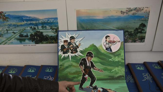 A North Korean teacher holds open a children's pop-up book, which depicts a U.S. soldier killing a Korean woman with a hatchet, in a library room at Kaeson Kindergarten in central Pyongyang on Saturday, March 9, 2013. For North Koreans, the systematic indoctrination of anti-Americanism starts as early as kindergarten. (AP Photo/David Guttenfelder)