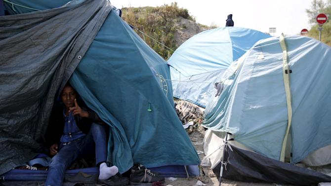 "An Ertirean migrant sits in his makeshift shelter in ""The New Jungle"" near Calais"