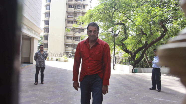 Bollywood actor Sanjay Dutt, center, stands outside his home after being temporally freed for two weeks from an Indian prison in Mumbai, India, Tuesday, Oct.1, 2013. The 54-year-old actor is currently serving five years in prison for illegal possession of weapons linked to Mumbai's 1993 terror attack. (AP Photo)