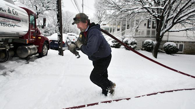 FILE - In this Wednesday, March 6, 2013, file photo, delivery truck driver Donald Whitacre, of Gore, Va., returns to his truck after pumping 200-gallons of home heating oil into a customer's tank during heavy snowfall in Winchester, Va. Chillier weather and slightly higher fuel prices may make the winter of 2013-14, the most expensive one in three years for U.S. residents. (AP Photo/The Winchester Star, Jeff Taylor, File)