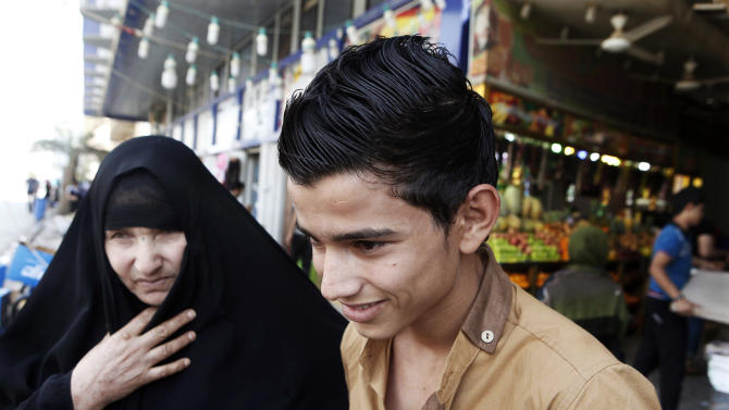 A mother with her young son shop at a market place in Kazimiyah neighborhood, northern Baghdad, Iraq, Sunday, Sept 2, 2012. A new culture rift is emerging in Iraq and, largely, at the seat of one of Shiite Islam's holiest sites as young women doff their shapeless cover-ups and men strut around in revealing slacks and edgy haircuts. This has prompted clerics to mobilize the fashion police in the name of protecting the Islamic nation's heritage. (AP Photo/Karim Kadim)